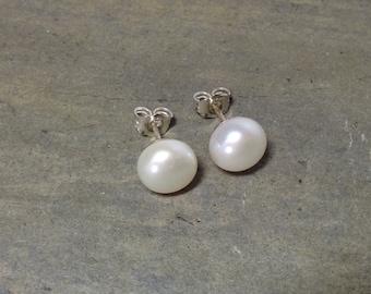 A pair of white pearl stud earrings.