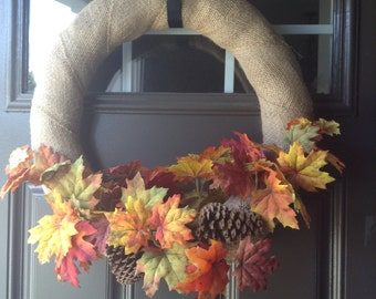 Fall burlap wreath featuring fall leaves and pinecones
