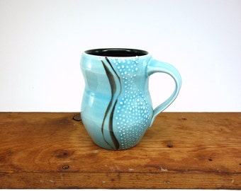 Blue glazed curvy porcelain mug with slip trailed dots
