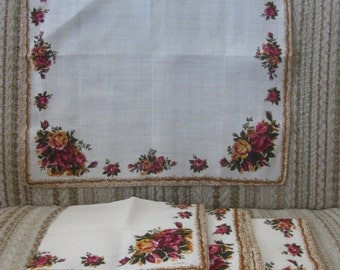 A Set of Four Linen Placemats With Red and Orange and Roses
