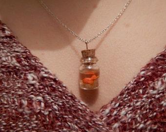 Colgante: pequeño pececito hecho y pintado a mano nadando en una botella