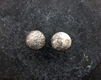 Leather look, textured silver stud earrings.