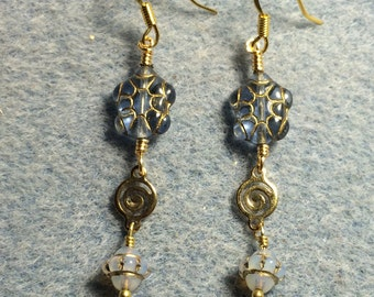 Light blue Czech glass turtle bead dangle earrings adorned with gold swirly connectors and light blue opal Saturn beads.