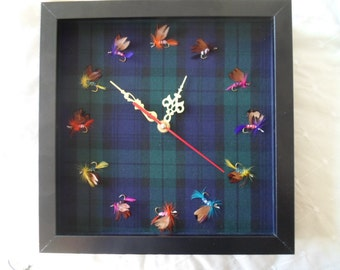 Fishing flies clock on tartan material background
