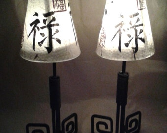 A pair of lanterns made from iron and glass