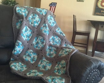 gray and variegated turquoise granny square throw