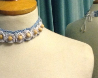 Crochet collar with wooden beads in the flowers on a velvet ribbon