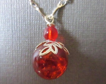 handmade red fried glass marble pendant ball necklace enhanced by a silver toned leaf design bead cap hung from a silver plated chain