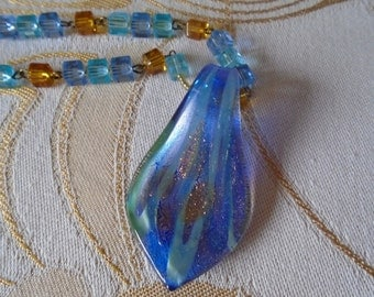 Glass pendant on amber coloured and blue glass beads