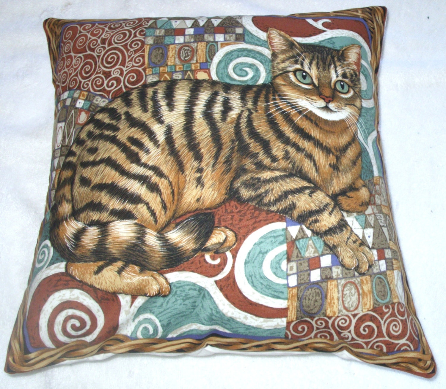 Tabby Cat Sitting On A Mosaic Patterned Rug In A Wicker Basket
