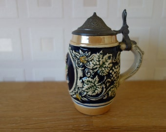Minature lidded beer stein with embossed decoration