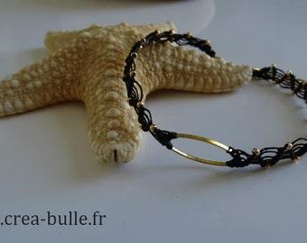 Bracelet woven in black macrame around a golden ring