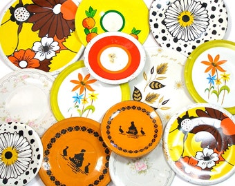 13 Tin Toy tea saucers in yellow, orange, black, 1950s graphics, Instant Collection.
