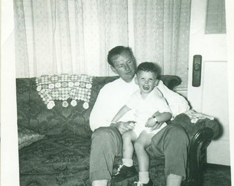 Father And Son 1940s Sitting in Daddy's Lap On Couch Happy Boy 40s Vintage Black and White Photo Photograph