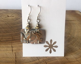 Textured Recycled shed flashing earrings with pewter bunnies jumping.