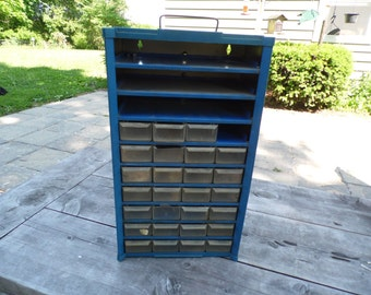 """Blue Metal Cabinet vintage free stand cabinet with 10 shelves and 27 clear plastic drawers 17"""" tall 9 1/2"""" across front 6"""" wide"""