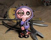 Naily, a creepy and cute mini monster dressed in purple. His head is full of real nails. Hellraiser tribute