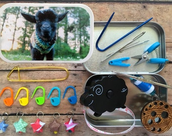 Baby goat in a sweater: Stitch markers - mini scissors - sheep tape measure - knitting needle gauge - travel notions for your project bag
