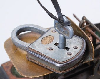 Vintage small metal padlock with key