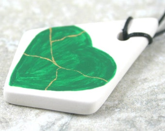 CLEARANCE SALE - Green kintsugi (kintsukuroi) inspired heart with gold repair on large porcelain bisque pendant on black cotton cord - OOAK