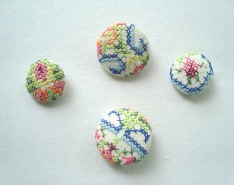 Four vintage embroidery covered buttons