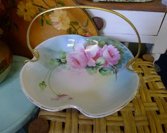 Porcelain clover shaped footed floral bowl with metal handle