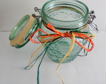 Vintage, green glass, embossed fruit themed jar, with sealed, attached lid.
