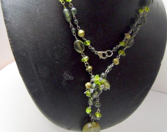 Necklace made of silver and green glass beads, with unique pendant. 32""