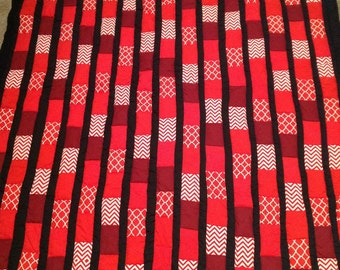 Cherries jubilee handmade patchwork red quilt outlined in black. Backing is a with cherry pattern.