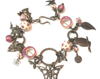 Bracelet with Butterflies Birds and Flowers Vintaj Natural Brass Charms and Raspberry Pink and Cream Ceramic Beads and Circles