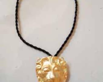 gilt lion necklace on silk cord