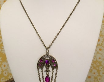 Antique gold chain necklace with ornate purple crystal pendant