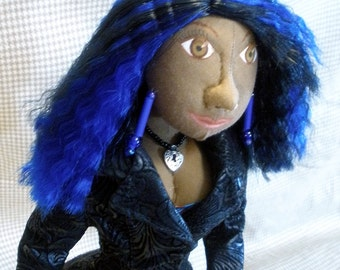 Rae is a cloth doll standing 18 inches tall, dressed in grey tweed pants and a faux leather jacket, with blue and black hair