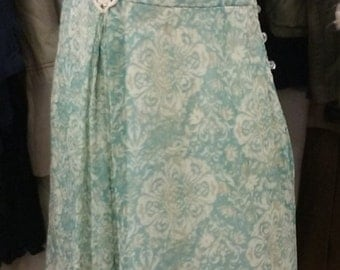 Plunging neckline leads to Crochet accent, Glass like Buttons cascade over left hip, Vintage inspired
