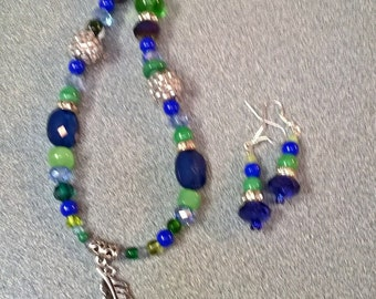 Blue and green beaded necklace with feather pendant.