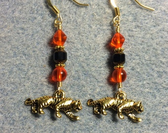 Gold tiger charm earrings adorned with orange and black Czech glass beads.