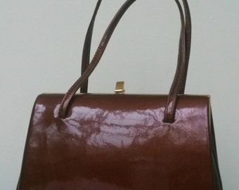 Shiny Bronze Colour Patent Leather Handbag; Gold Cross Label Inside Bag, & Suede Lining.