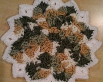 Crocheted flower trivet in green and brown tones