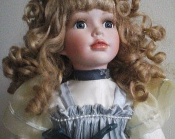 Porcelain doll girl in blue dress with Ribbon