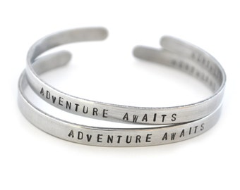 "Set of 2 ""Adventure Awaits"" metal bracelet bangles"