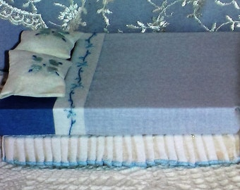Mini doll bed in blue with bedding on wooden base.
