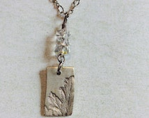 Fine silver leaf imprint pendant necklace. Clear faceted czech glass beads.Sterling silver chain.