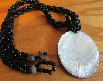 Black beaded necklace with carved shell pendent