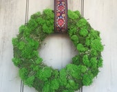 Lush moss wreath made with preserved moss. With vintage tapestry ribbon.