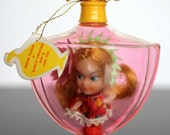 Perfume Playmates tiny doll in a bottle by Sarco 1960's toy blonde in red dress with flowers with tag screw top plastic cologne display pink