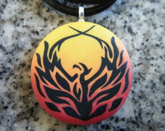 Phoenix fire design hand carved on a polymer clay red orange and yellow pearl blend background. Pendant comes with a FREE 3mm Necklace