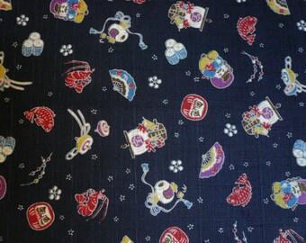 Tissu japonais avec motifs petits personnages daruma, poissons , fond bleu marine, trame irrégulière - 50 cm
