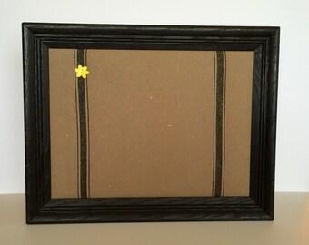 Black framed tan/black stripe fabric covered bulletinboard