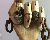 Assemblage art wood hand and rusty gears Altered wood hand with a leather cuff