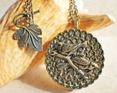 Music box locket, round bronze locket with music box inside, with a bronze filigree and a bronze birds on front cover.